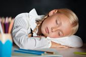 Tired school girl sleeping during lesson
