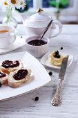 Fresh toasts with homemade butter and blackcurrant jam on wooden table, on bright background