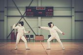 stock photo of rapier  - Two women fencers on a training  - JPG