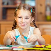 happy cute little girl is engaged in needlework at home