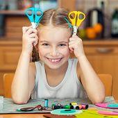 happy cute little girl shows two scissors