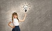 Cute schoolgirl pointing on electrical bulb with finger
