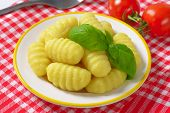 plate of cooked gnocchi on checkered tablecloth