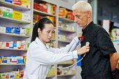 chinese pharmacist chemist woman examining heartbeat of customer in china pharmacy drugstore