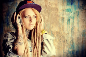 stock photo of dreadlock  - Trendy teenage girl with blonde dreadlocks listening to music on headphones - JPG