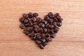 picture of tamarind  - pile of tamarind seed in shape heart on wooden background - JPG