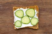 foto of cucumber slice  - fried toast with soft cheese and cucumber slices on vintage wood - JPG