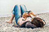 stock photo of sleeping  - Beagle puppy sleeping on his owner breast at the sea side - JPG