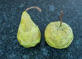 stock photo of bast  - Green pear and apple made from bast fibre laying on the dark granite - JPG
