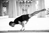 pic of urbanization  - Man practicing advanced yoga in a urban background - JPG