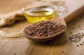 picture of flax seed oil  - Brown flax seeds on a spoon and flaxseed oil on a wooden table - JPG