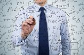 stock photo of subtraction  - young businessman drawing mathematics equations and formulas - JPG