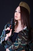 picture of cap gun  - Young woman in the military uniform with the gun over black background - JPG