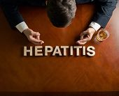 image of hepatitis  - Word Hepatitis made of wooden block letters and devastated middle aged caucasian man in a black suit sitting at the table with the glass of whiskey - JPG