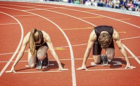 stock photo of sprinters  - Track and field photo of a sprinter couple kneeling in start position ready to start in a curve of a stadium - JPG