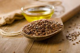 stock photo of flax seed oil  - Brown flax seeds on a spoon and flaxseed oil on a wooden table - JPG