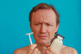 stock photo of razor  - a man to shave but is undecided whether to choose razor or razor - JPG