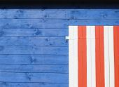 pic of ou  - corner of a closed white door or window with red stripes on a blue wall coin d - JPG