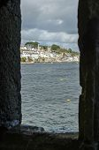 foto of pov  - Looking through one of the late medieval slit windows of the Tudor Blockhouse at Polruan in Cornwall Across the River to the Popular Tourist Destination and Fishing Village of Fowey - JPG