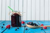 foto of mason  - Mason jar with berry jam or marmalade and fresh raspberry on a rustic wooden table - JPG