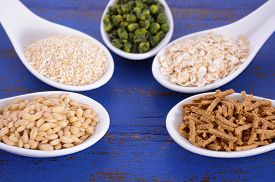stock photo of oats  - Healthy High Fiber Prebiotic Grains in serving spoons including wheat bran cereal oat flakes dried legume peas oat bran and pearl barley on rustic dark blue wood table - JPG