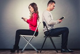 picture of not talking  - Couple using mobile phones not talking to each other - JPG