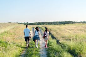 pic of girl walking away  - Young people walking away along country path - JPG