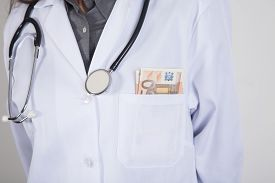 picture of hospital gown  - woman doctor with white gown and stethoscope with a wad of Euro banknotes in her pocket - JPG