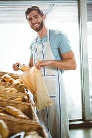 stock photo of tong  - Smiling waiter taking bread with tongs at the bakery - JPG