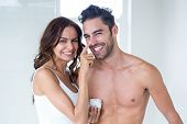Portrait wife smiling while applying cream on husband face at home poster