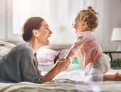 Happy loving family. Young mother are playing with her baby girl in the bedroom. Mom and child are h poster