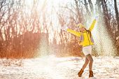 Winter snow fun woman playing throwing snow celebrating cold weather. Girl in yellow outerwear glove poster