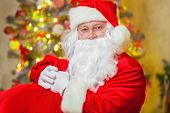 Santa Claus With Giftbox On Background Of Sparkling Firtree poster