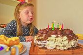 Little Girl Blowing Out Candles On Her Birthday Cake. Small Girl Celebrating  Her Six Birthday. Birt poster