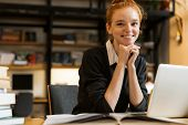 Smiling red haired teenage girl using laptop computer at the library poster