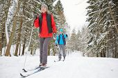 Active mature spouses in sportswear enjoying ski training on winter day in the forest poster