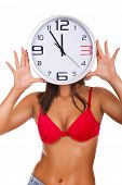 young naked woman holding clock on face on white background