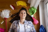 Top View Of A Housekeeping Assistant Lying On The Floor Encircled With Housekeeping Tools, Mops, Bro poster
