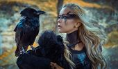 Beautiful black crow, Viking blonde woman with shield and sword, braids in her hair. poster