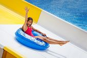 Beautiful Girl On Inflatable Ring Riding Water Slide With Hand Up In Aqua Park poster