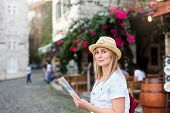 Girl Traveler Is Smiling With City Map, Searching Italian Authentic Street Restaurant. Woman Tourist poster
