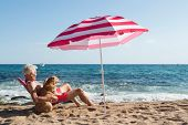Senior man sun bathing with his dog at the beach under parasol with waves, sea and sand poster