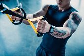 Cropped View Of Young Muscular Sportsman Training With Resistance Bands In Gym poster