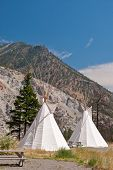 picture of tipi  - Row of beautiful cabins in a form of traditional indian tipi over gorgeous mountain view - JPG