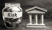 A Glass Jar And The Inscription risk Stands Next To A State Building. The Concept Of Financial And poster