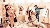Happy Children With Parents Having Pillow Fight. Kids And Parents Having Pillow Fight On Bed At Home poster