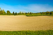 Close-up of a sand bunker on the golf course with green grass and trees over blue sky.