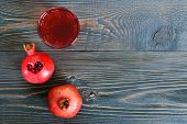 Ripe Pomegranate Fruit And A Glass Of Pomegranate Juice On Wooden Table. Healthy Eating Concept. Cut poster