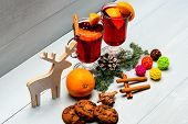 Winter Beverage Concept. Glasses With Mulled Wine Or Hot Drink Near Wooden Deer Decoration On White  poster