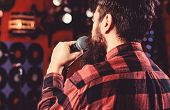 Musician With Beard Singing Song In Karaoke, Rear View. Rock Singer Concept. Guy Likes To Sing In Da poster